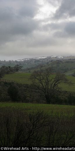 A snowcapped mountain against the green grass, near Mt. Hamilton in Silicon Valley.